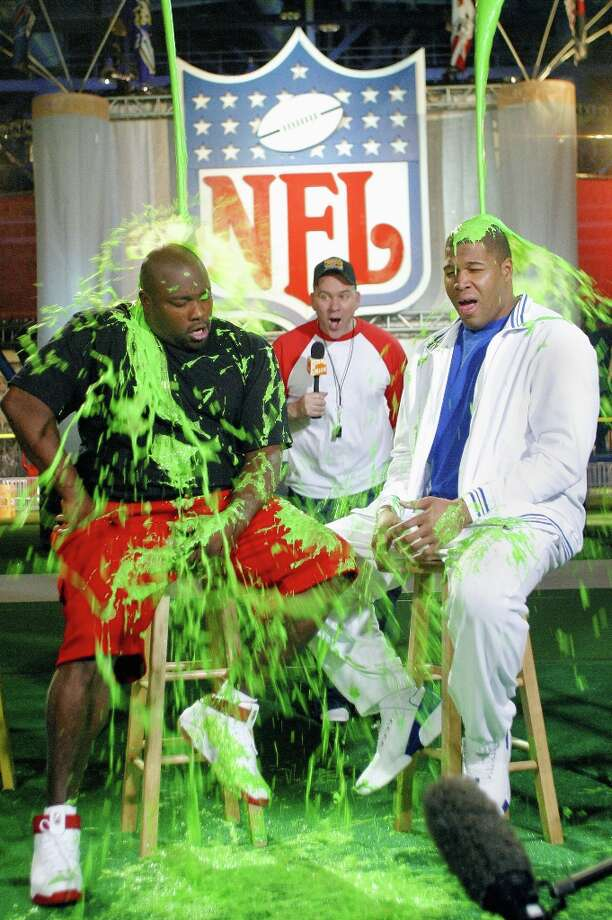 Mike O'Malley of CBS' Yes, Dear looks on as Warren Sapp of the Tampa Bay Buccaneers and Michael Strahan of the NY Giants get slimed during the taping of Nickelodeon Takes Over The Super Bowl in 2004 in Houston. Photo: Getty Images / Nickelodeon