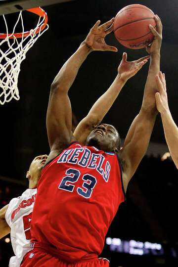 Reginald Buckner #23 of the Ole Miss Rebels rebounds against Ryan Evans #5 of the Wisconsin Badgers