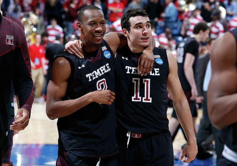 Will Cummings #2 and T.J. DiLeo #11 of the Temple Owls walk off the court after defeating the North