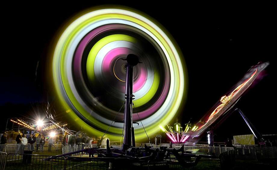 Round and round: A Ferris wheel and other rides spin in a 25-second time-exposure photo taken during the Trussville Spring Carnival in Trussville, Ala. Photo: Mark Almond, Associated Press