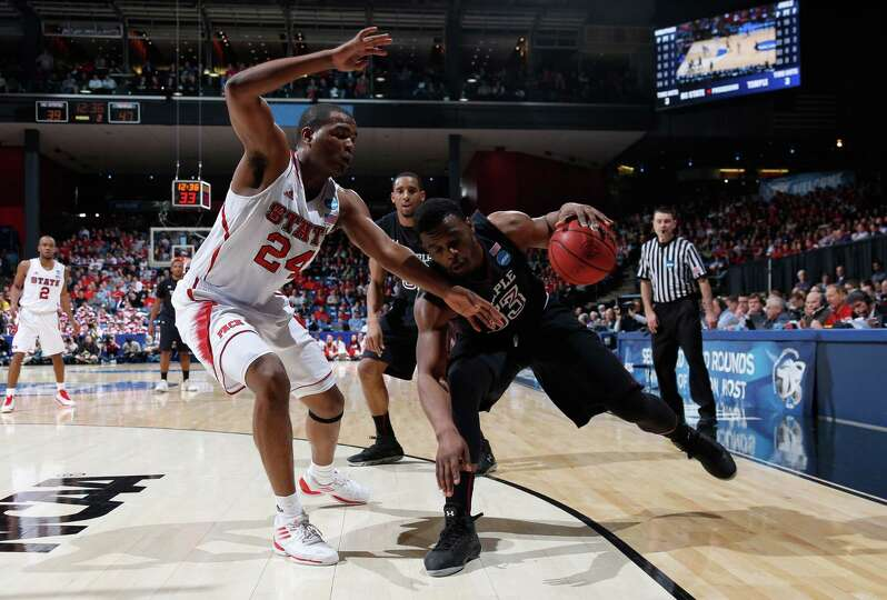 Scootie Randall #33 of the Temple Owls handles the ball against T.J. Warren #24 of the North Carolin
