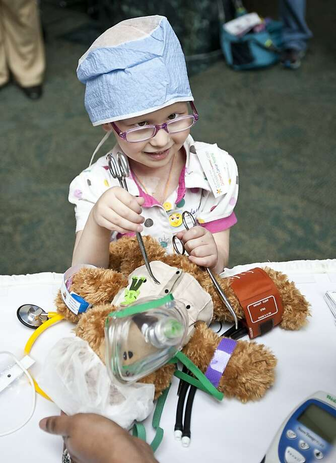 I need more Kelly clamps, stat! Dr. Hannah Meeson, 5, performs an emergency sawdustectomy on Teddy the bear at Anderson Children's Cancer Hospital in Houston. Photo: Nick De La Torre, Houston Chronicle