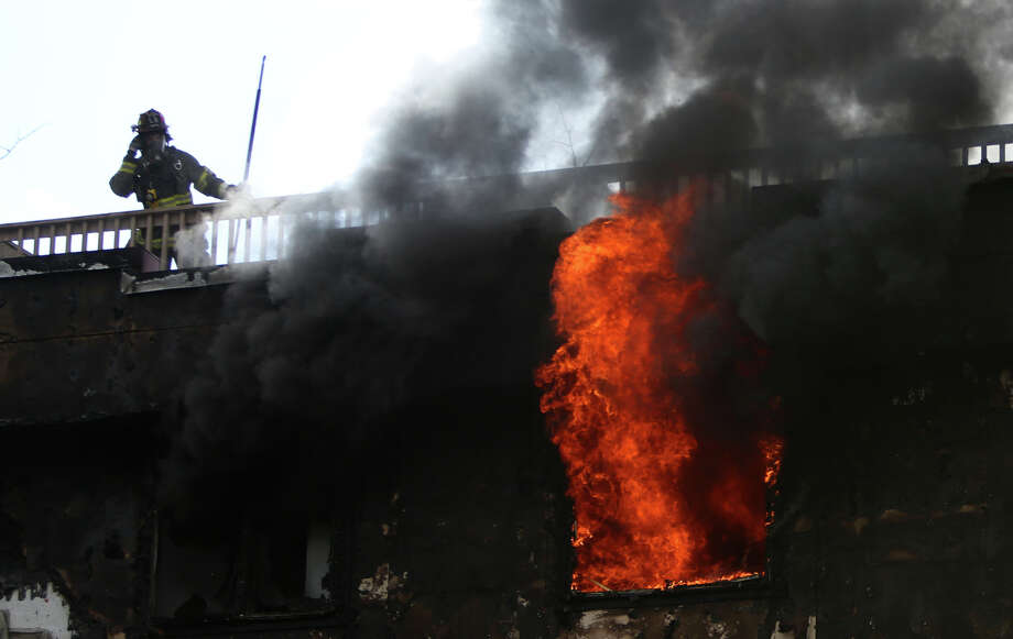 A Seattle firefighters stands over a burning apartment as crews battle a four-story apartment fire on Friday, March 22, 2013 in Seattle's Pinehurst neighborhood. The fire damaged six units of the building and was apparently started by a burning motorcycle. Photo: JOSHUA TRUJILLO / SEATTLEPI.COM