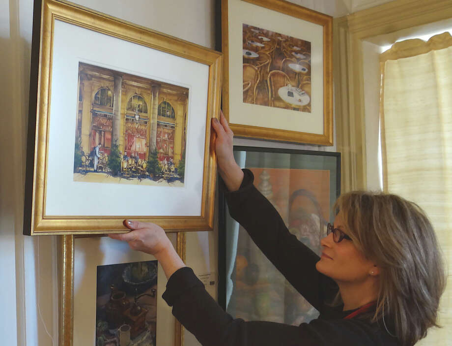 Junior League of Eastern Fairfield County volunteer Jennie Julio takes down a painting that was quickly sold Friday at the group's 21st annual Art Show at the Burr Homestead. FAIRFIELD CITIZEN, CT 3/22/13 Photo: Mike Lauterborn / Fairfield Citizen contributed