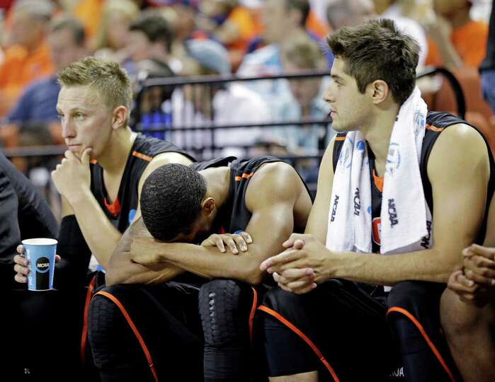 Pacific players react on the bench during the second half of a second-round game of the NCAA college