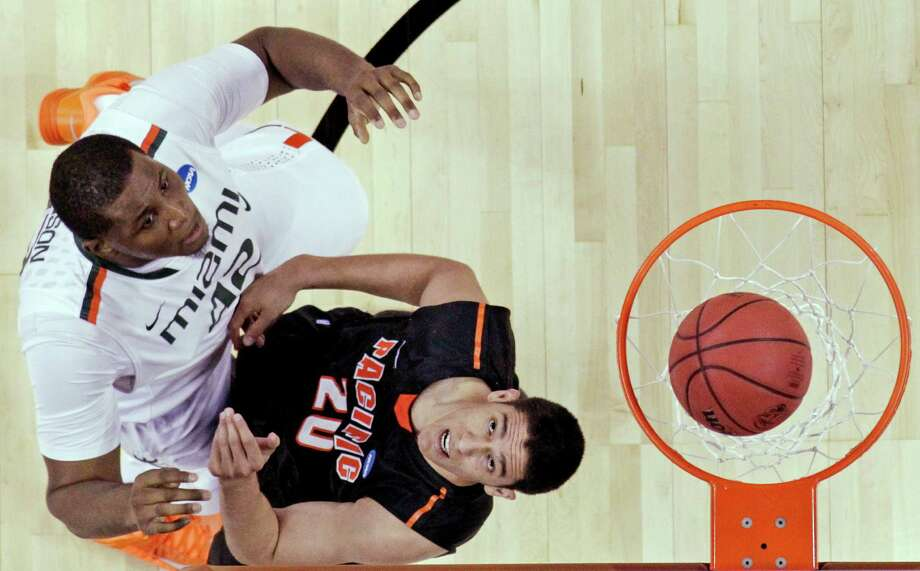 Miami's Reggie Johnson (42) shoots over Pacific's Ross Rivera (20) during the second half of a second-round game of the NCAA college basketball tournament Friday, March 22, 2013, in Austin, Texas.  (AP Photo/David J. Phillip) Photo: David J. Phillip, Associated Press / AP