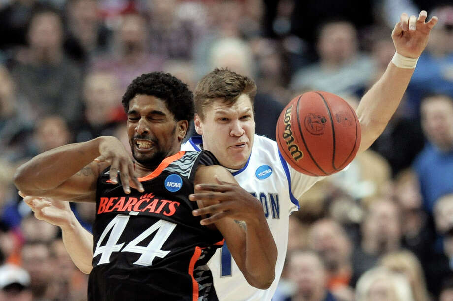 Cincinnati's JaQuon Parker, left, and Creighton's Grant Gibbs collide during the first half of a second-round game of the NCAA college basketball tournament, Friday, March 22, 2013, in Philadelphia. (AP Photo/Michael Perez) Photo: Michael Perez, Associated Press / FR168006 AP