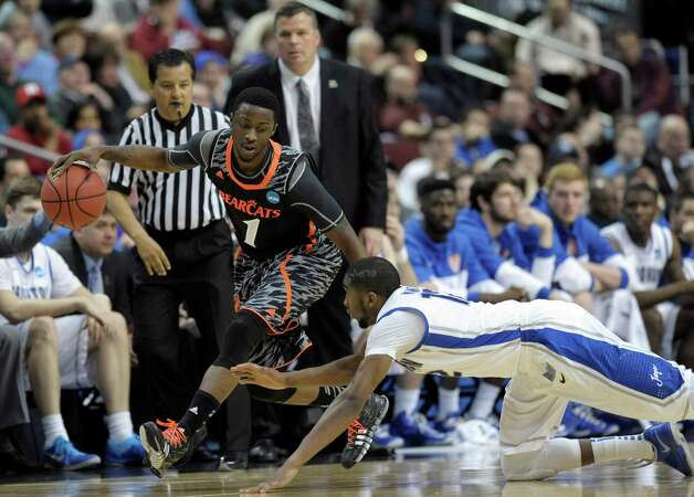 Cincinnati's Cashmere Wright, left, dribbles past a diving Creighton's Jahenns Manigat during the first half of a second-round game of the NCAA college basketball tournament, Friday, March 22, 2013, in Philadelphia. (AP Photo/Michael Perez) Photo: Michael Perez, Associated Press / FR168006 AP