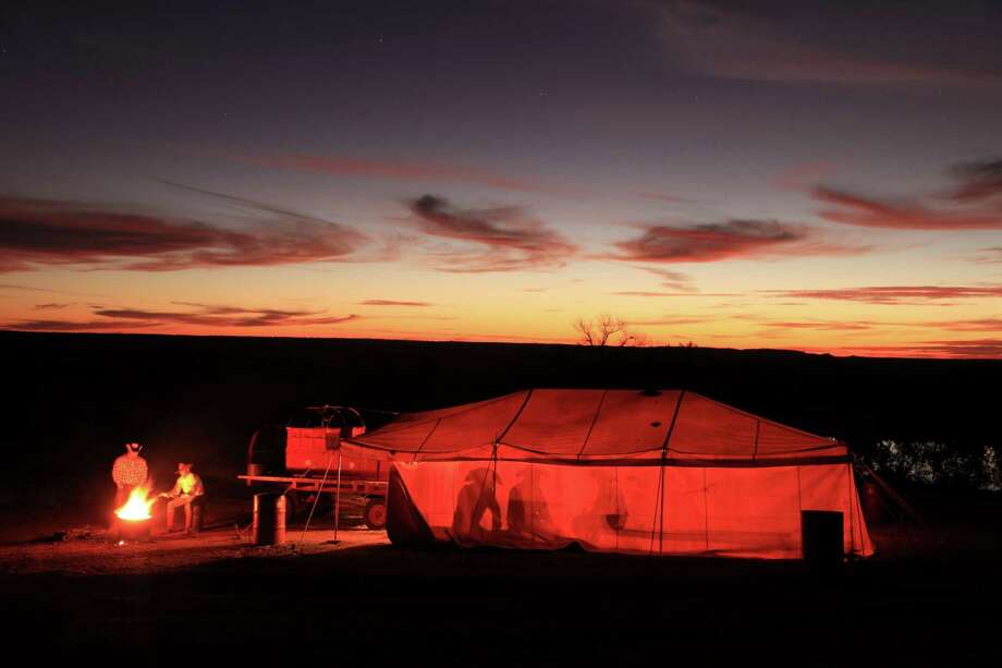"""Cowboys sit by a campfire in this 2009 image made for Wyman Meinzer's book: """"Under one Fence: The Waggoner  Ranch Legacy."""" (More: The state photographer has seen it all) Photo: Wyman Meinzer / © 2009 Wyman Meinzer"""