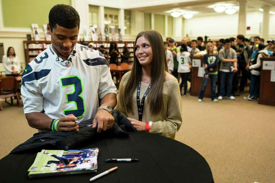 "Roosevelt High School junior Aly Martineau, center, watches in admiration as Russell Wilson, left, quarterback of the Seattle Seahawks, signs her jacket during his congratulatory visit to Roosevelt High School in Seattle on Friday, March, 22, 2013. Roosevelt was the winner of the Verizon Wireless ""Save It Seattle"" contest, which challenged students at four local high schools to take pledges against the dangerous practice of texting and driving. Photo: JORDAN STEAD / SEATTLEPI.COM"