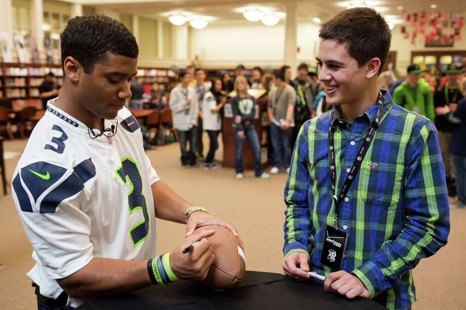 Russell Wilson, left, greets student fans. Photo: JORDAN STEAD / SEATTLEPI.COM