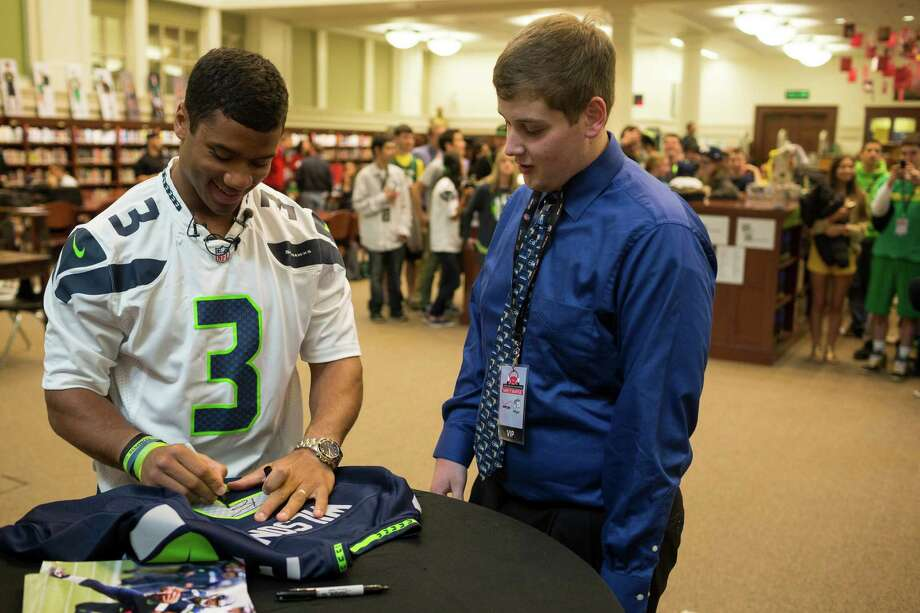 Roosevelt High School senior Logan Flanner, center, gets his jersey signed by Russell Wilson. Photo: JORDAN STEAD / SEATTLEPI.COM