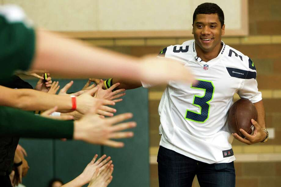 Russell Wilson makes a round of high fives to students. Photo: JORDAN STEAD / SEATTLEPI.COM
