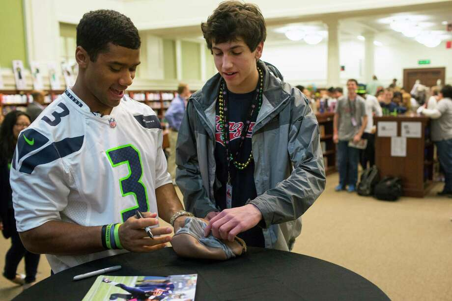 Student Hank Reimers, center, has Russell Wilson, left, sign a Tupac mask he found in his car. Photo: JORDAN STEAD / SEATTLEPI.COM