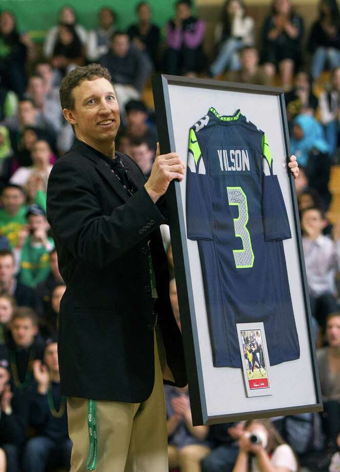 Roosevelt High School Principal Brian Vance,shows off a Russell Wilson-signed jersey. Photo: JORDAN STEAD / SEATTLEPI.COM