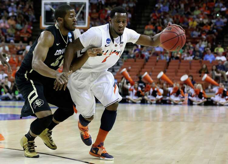 D.J. Richardson #1 of the Illinois Fighting Illini dribbles past Jeremy Adams #31 of the Colorado Bu