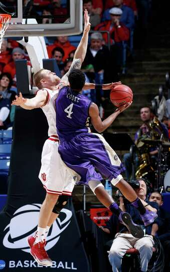 Charles Cooke #4 of the James Madison Dukes drives to the basket against Derek Elston #32 of the Ind