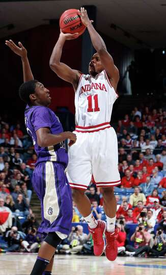 Yogi Ferrell #11 of the Indiana Hoosiers shoots against Ron Curry #2 of the James Madison Dukes.