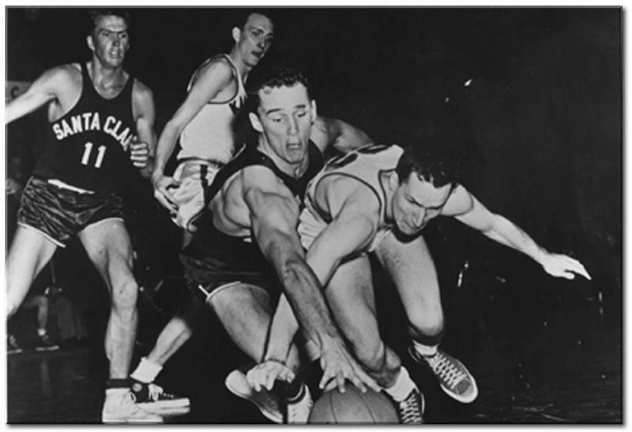 1952: The Final Four was again hosted at UW's Hec Ed in 1952, when the tourney consisted of 16 teams. In this photo, Dean Smith (far right) of the University of Kansas dives for a lose ball during the NCAA Final Four national semifinal against Santa Clara University on March 25, 1952, in Seattle. The Jayhawks beat the Broncos 74-55. Kansas went on to win the national championship game March 29, beating St. John's University 80-63.