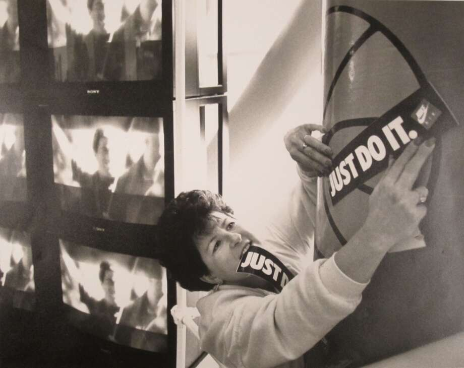 1989:The caption for this March 19, 1989, P-I photo reads: ''Karin Morlan, Nike sports promotional manager, puts up stickers of the company's slogan next to the ESPN television monitors at Westlake Center. Nike has pulled out all the stops on its Final Four promotion drive.''