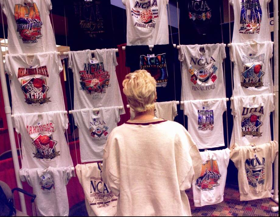 1995:The caption to this March 30, 1995, P-I photo reads: ''A visitor to the Washington Convention Center looks at T-shirts with NCAA logos that are for sale.''