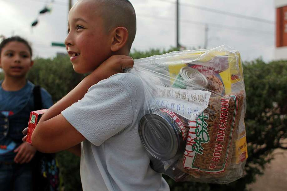 Port Houston Elementary School student Marvin Hernandez holds a bag of food the school gives to families in need for the weekend.  The food is provided by the Houston Food Bank. HISD has started serving dinner for a small number of their schools. Port Houston Elementary has been serving dinner since November to about 150 students a day. Photo: Johnny Hanson, Houston Chronicle / © 2013  Houston Chronicle