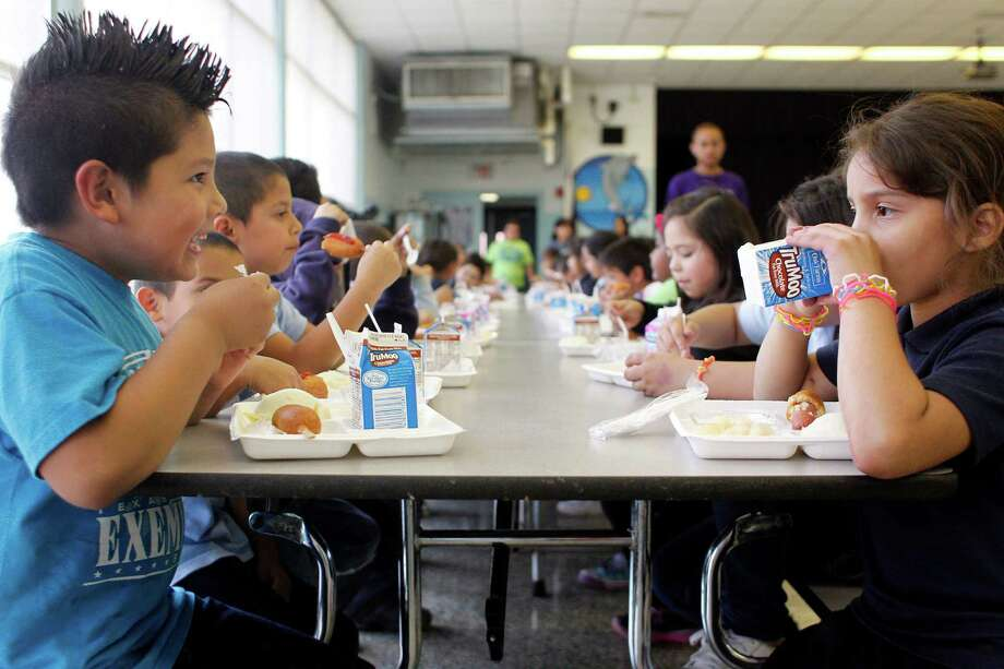 Second graders, Richardo Tellez, 8, and Stephanie Riveria, 8, eat dinner with about 150 Port of Houston Elementary School in the school cafeteria in Houston. HISD has started serving dinner for a small number of their schools. Port Houston Elementary has been serving dinner since November to about 150 students a day. Photo: Johnny Hanson, Houston Chronicle / © 2013  Houston Chronicle