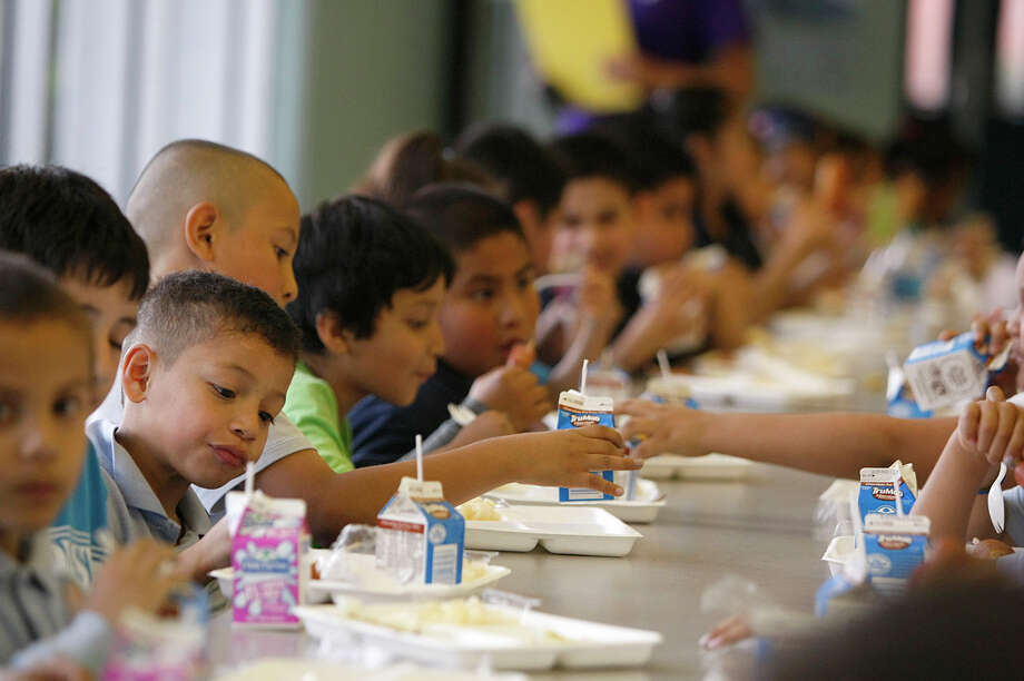 First grader Henry Hernandez eats dinner with about 150 Port of Houston Elementary School in the school cafeteria. Photo: Johnny Hanson, Houston Chronicle / © 2013  Houston Chronicle