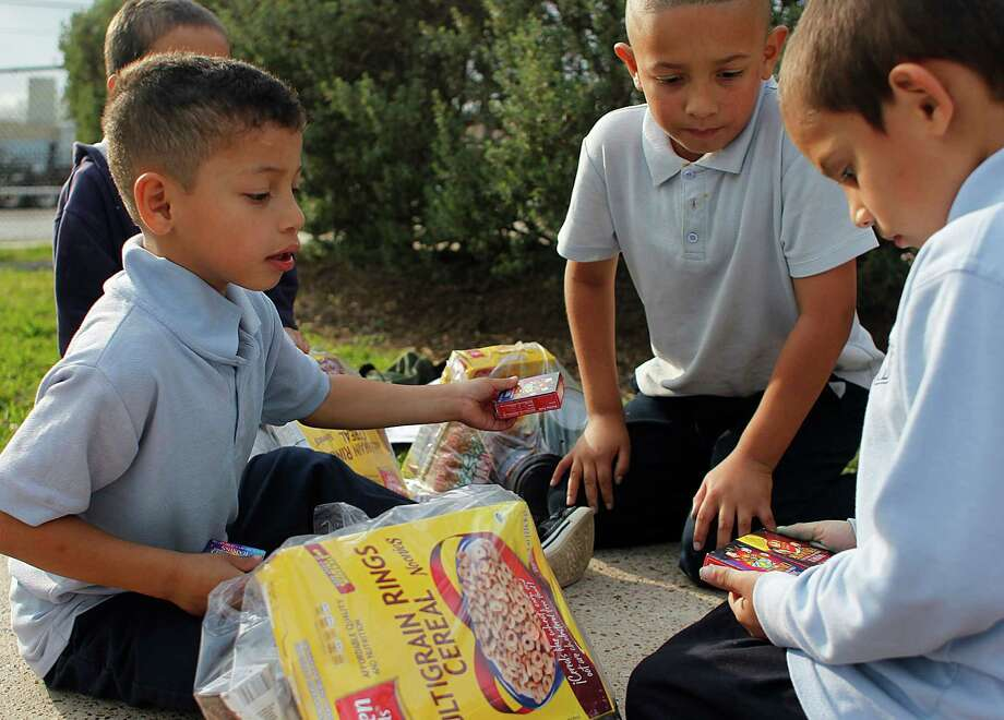 A group of Port Houston Elementary School students look through their bags of food the school gives to families in need for the weekend. Photo: Johnny Hanson, Houston Chronicle / © 2013  Houston Chronicle