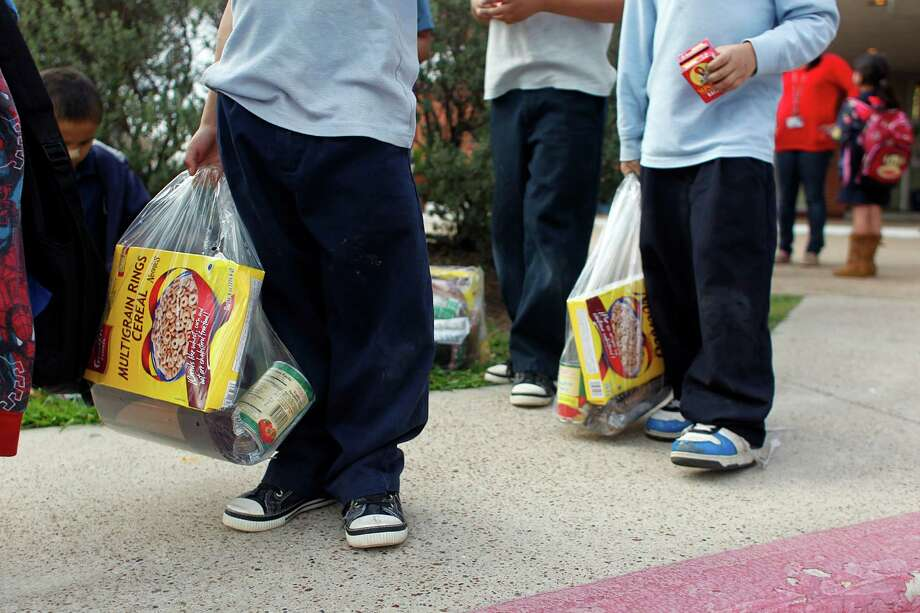 A group of Port Houston Elementary School students hold bags of food the school gives to families in need for the weekend. Photo: Johnny Hanson, Houston Chronicle / © 2013  Houston Chronicle