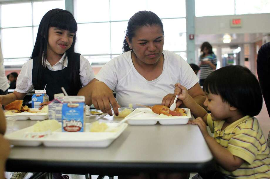 Stephanie Lopez, a first grader at Port of Houston Elementary School, sits with her mother, Yessenia Lopez, and her one-year-old brother, Steven, as she and Steven eat dinner at the school. Photo: Johnny Hanson, Houston Chronicle / © 2013  Houston Chronicle