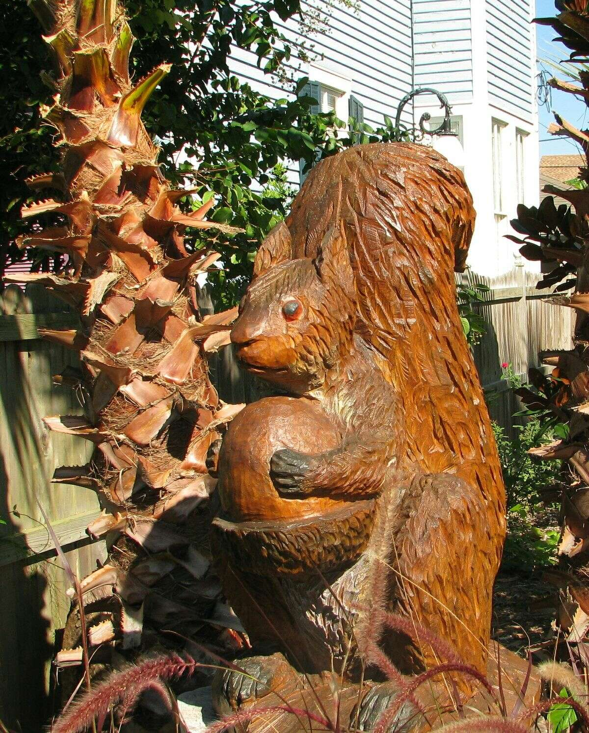 A squirrel clutches an acorn in this hurricane tree sculpture in Galveston.