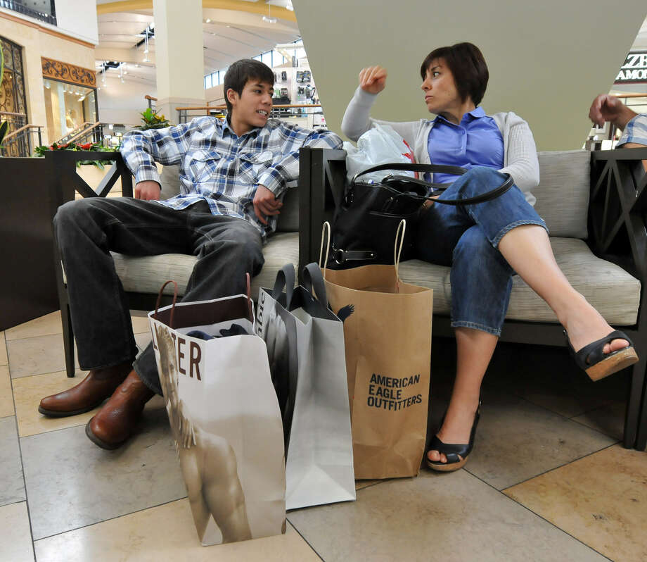 Julio Perez chats with his mother, Lyderie Perez, Durango, Mexico, while taking a break from shopping at North Star Mall in this file photo. Mexican nationals traditionally cross the border to San Antonio for shopping vacations during Holy Week. Photo: Express-News File Photo
