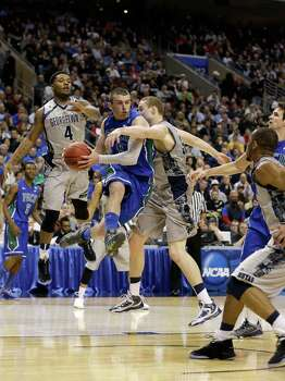 Brett Comer #0 of the Florida Gulf Coast Eagles looks to pass the ball in the second half as he drives against Nate Lubick #34 and D'Vauntes Smith-Rivera #4 of the Georgetown Hoyas during the second round. Photo: Rob Carr, Getty Images / 2013 Getty Images