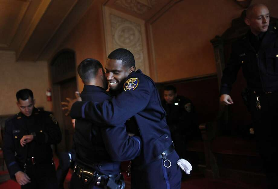 Cedric Remo hugs a classmate from the Oakland Police Department's 166th Basic Academy as they graduate. Photo: Lea Suzuki, The Chronicle