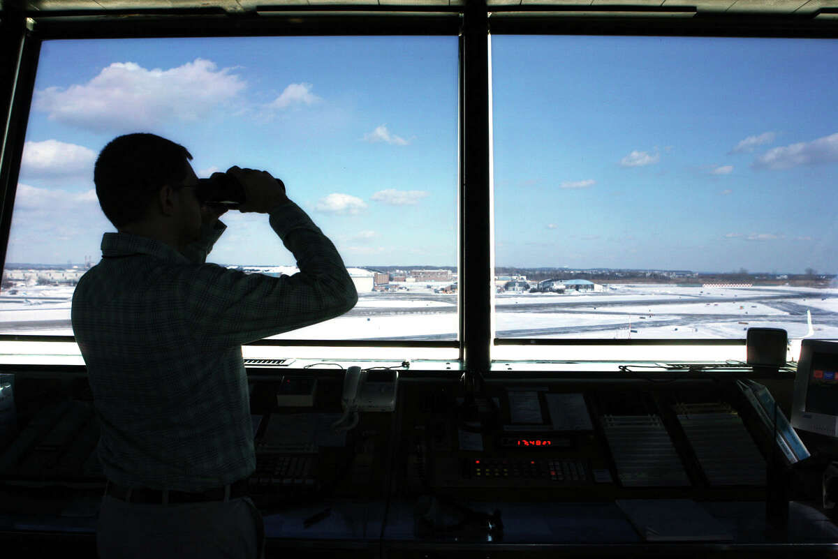Air Traffic Control Specialist Eric Lanier checks on an incoming plane from the tower at Sikorsky airport in Stratford. 1/16/09
