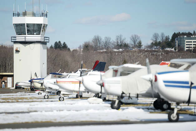 Parked planes line the airfield up to the control tower at the Danbury Municipal Airport in Danbury, Conn. on Wednesday, March 20, 2013.  A proposed federal budget cut recommended by the Office of Management and Budget would eliminate the budget to staff employees for several privately owned airport control towers, like the one at Danbury Airport, which would shut down the control tower operation. Photo: Tyler Sizemore / The News-Times