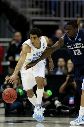 James Michael McAdoo #43 of the North Carolina Tar Heels drives against Mouphtaou Yarou #13 of the V