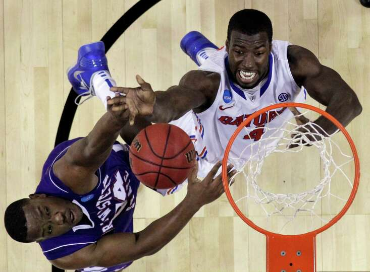 Florida's Patric Young (4) goes up for a shot as Northwestern State's Gary Roberson (34) defends dur