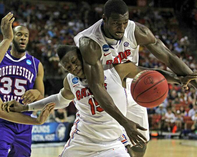 Florida Gators' Will Yeguete (15) and Patric Young (4) attempt to save the ball from going out of bo
