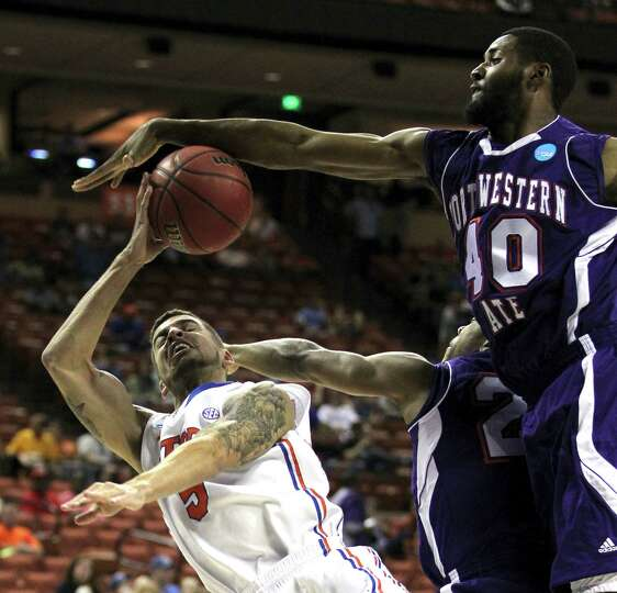The Florida Gators' Scottie Wilbekin gets blocked under the basket by the Northwestern State Demons'