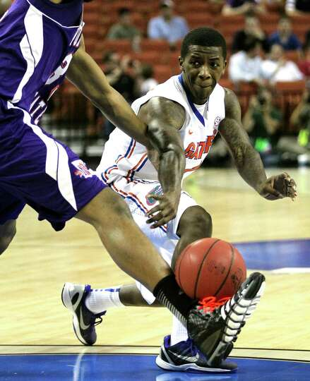 The Florida Gators' Kenny Boynton passes the ball into the leg of a Northwestern State Demons defend