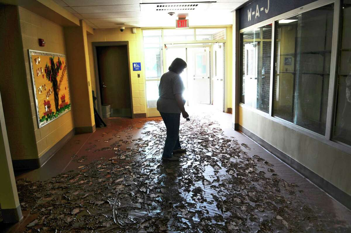 Mud coats the floors of the Windham Ashland Jewett Central School, damaged as a result of Tropical Storm Irene, on Wednesday Aug. 31, 2011, in Windham, NY. Michelle Mattice, treasurer of the school district, walks through the hall. (Philip Kamrass / Times Union)