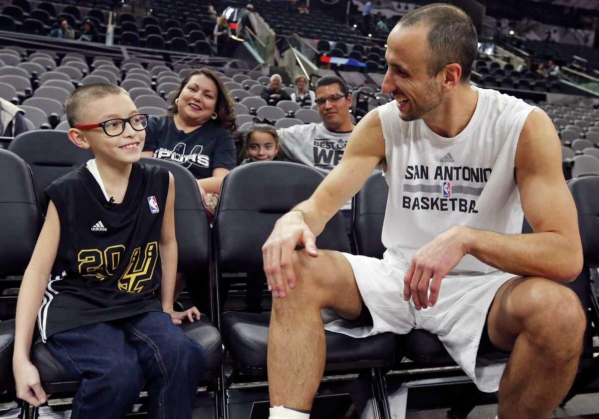 Ginobili San Miguel-Ramirez, 10, talks with San Antonio Spurs' Manu Ginobili before the Spurs and Utah Jazz game as his mother Renee San Miguel-Ramirez, 36, (rear from left) sister Georgina San Miguel-Ramirez, 8, and father Jorge Ramirez, 38, look on Monday Dec. 14, 2015 at the AT&T Center.
