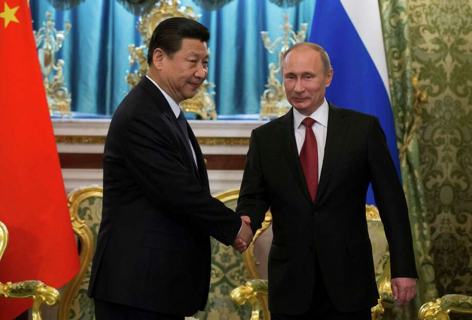 Russian President Vladimir Putin, right, and Chinese President Xi Jinping shake hands during their meeting in the Kremlin in Moscow, Russia, Friday, March 22, 2013. Russia is Xi Jinping's first foreign destination as China's president. Xi's talks with Putin on Friday are set to focus on oil and gas as China seeks to secure new energy resources to fuel its growing economy. (AP Photo/Alexander Zemlianichenko, Pool) Photo: Alexander Zemlianichenko