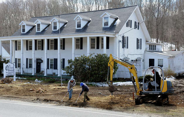 Crews from Quaker Farms Construction work to clean up property around Oxford House along Route 67 in Oxford, Conn. on March 22, 2013. Owner Jay Borkowski bought the landmark building and plans to develop it for potential business like a bakery, coffee house and professional offices upstairs. Photo: Christian Abraham / Connecticut Post