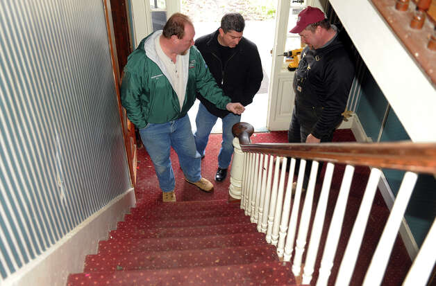 Oxford House owner Jay Borkowski, left, gives his friend John Bogart, center, a tour of the historic building along Route 67 in Oxford, Conn. on March 22, 2013.At right is Jay's brother Karl Borkowski who is doing a lot of the renovation. Jay bought the landmark building and plans to develop it for potential business like a bakery, coffee house and professional offices upstairs. Photo: Christian Abraham