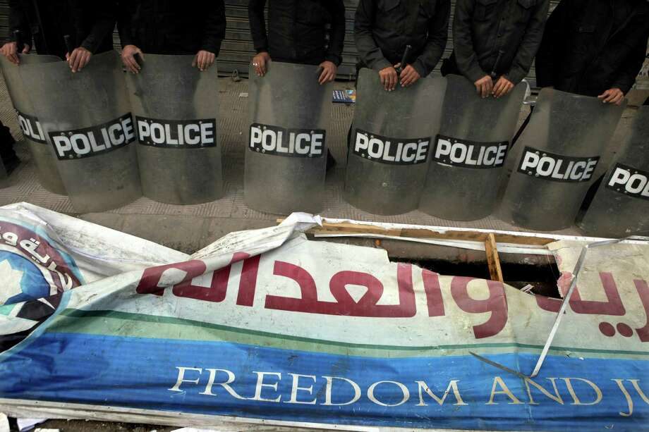 A destroyed banner of the Muslim Brotherhood's Freedom and Justice Party lay in front of anti-riot soldiers after protesters broke into a branch headquarters in Cairo. Photo: Amr Nabil / Associated Press