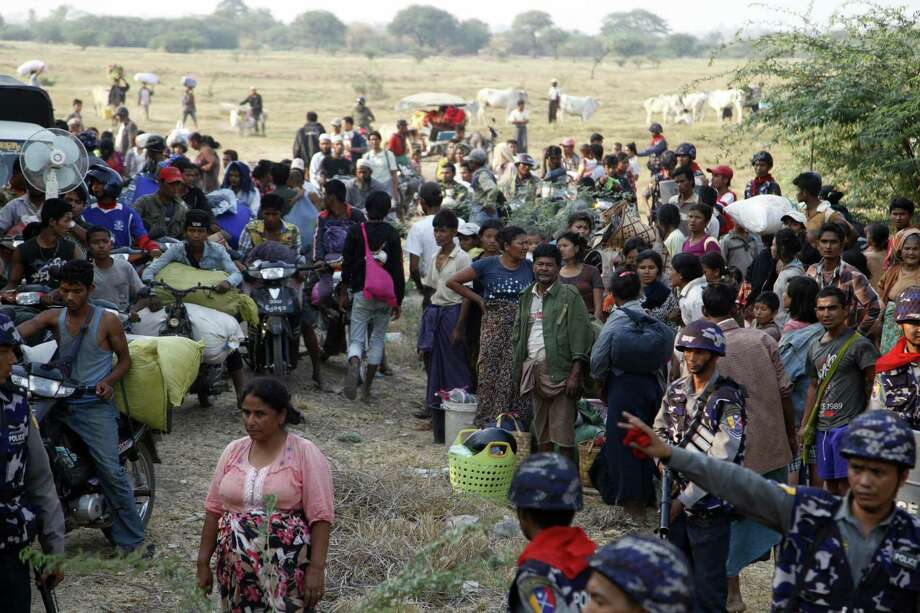 Carrying belongings, Muslim refugees try to move a rescue camp in Meikhtila, Myanmar. Thousands fled the city where unrest between Buddhists and Muslims erupted Wednesday. Photo: Khin Maung Win / Associated Press