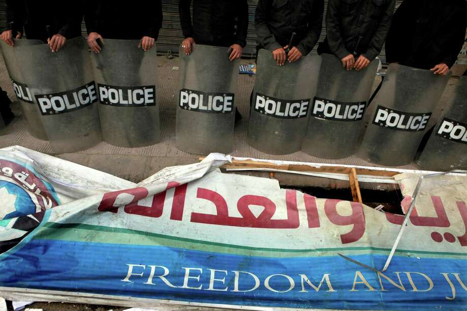 Egyptian anti-riot soldiers stand guard in front of a destroyed banner of the Muslim Brotherhood's Freedom and Justice Party after protesters broke into a branch headquarters in the Manial neighborhood in Cairo, Egypt, Friday, March 22, 2013. Thousands of opponents and supporters of Egypt's powerful Muslim Brotherhood clashed Friday near the Islamist group's Cairo headquarters, where riot police guarded the building. In another Cairo neighborhood, young protesters broke into the Brotherhood party's office in Manial and stole some items, according to security officials. (AP Photo/Amr Nabil) Photo: Amr Nabil
